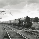 Date - 04/08/1962. Malton. Photo Ref 414.B1 4-6-0 no 61039 Steinbok passes Malton West box with a Saturday Paisley-Scarborough extra. On the left is a loading gauge - a metal frame suspended over the track to indicate the limits to which an open freight wagon could be safely loaded.©  A M Ross