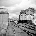 Date - 1956. Wharram. Photo Ref 385.View towards Malton with water tower, station platform and station house in view.  Some of the pick-up freight from Settrington (no.383)  can be seen 'parked' on the 'main line' while shunting is carried out. ©  A M Ross